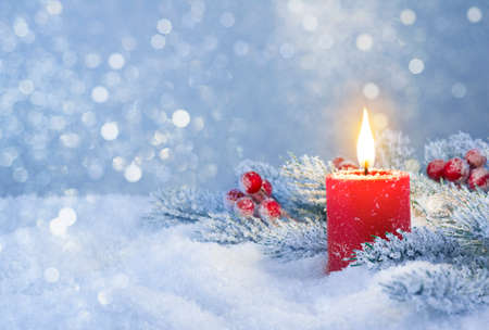 Burning candle in snow with festive decoration over frosty background Standard-Bild