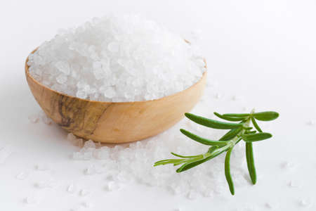 Sea salt bowl and fresh rosemary twig on white table