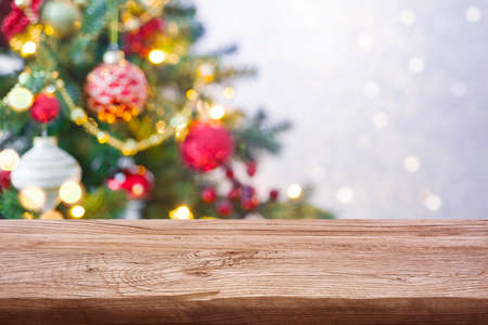 Holiday background concept of wooden table against decorated Christmas tree