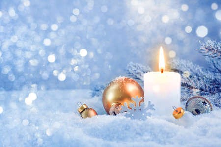 Burning candle and snowy holiday decoration over frosty lights background