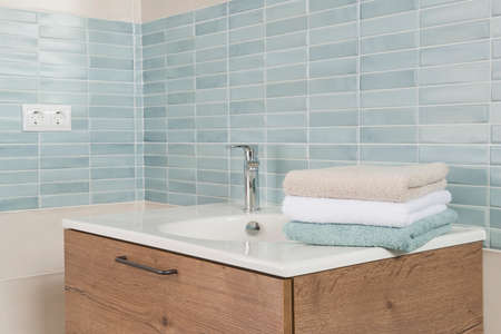 Stylish sink pedestal with several towels in modern bathroom interior Standard-Bild