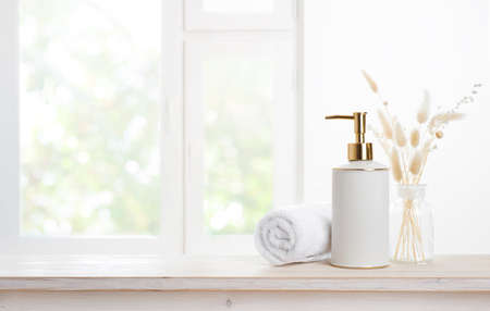 Towel and soap dispenser on table against blurred window background Standard-Bild