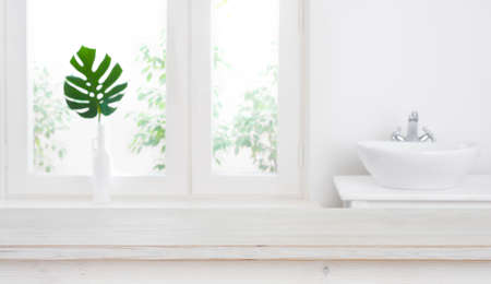 Empty table for product display against defocused bathroom window background