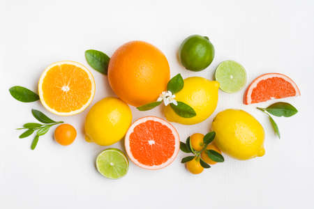 Citrus fruits and green leaves on white table top view Standard-Bild