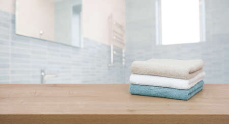 Cotton towels on wooden table in blurred bathroom interior background