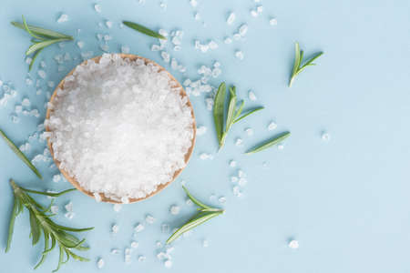 Sea salt and rosemary herb on blue background, top view