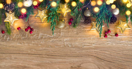 Holiday garland lights with Christmas tree decoration on wood background