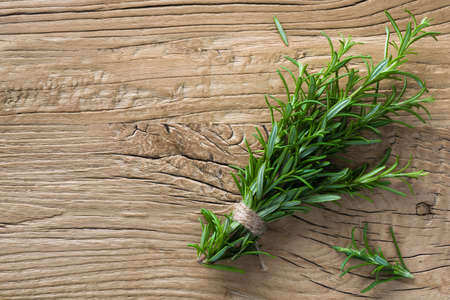 Bunch of rosemary herb on the rough wooden texture background