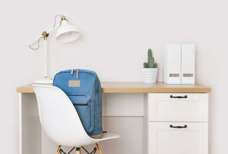 Wooden desk, supplies and school backpack on chair in room