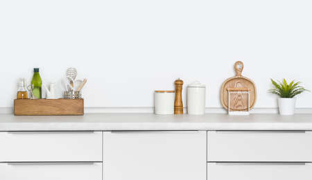 Contemporary utensils and spices standing on kitchen countertop with space