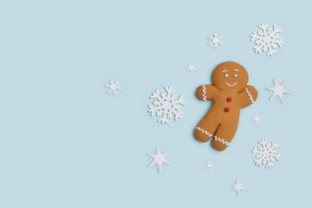 Classic gingerbread cookie hero isolated on blue with decorative showflakes Standard-Bild