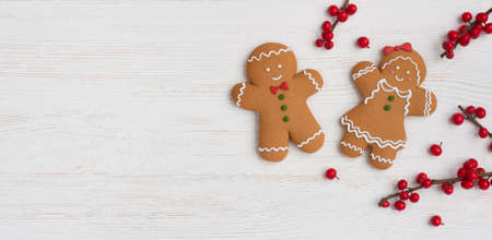 Homemade gingerbread man and woman with holly berry on wood Standard-Bild