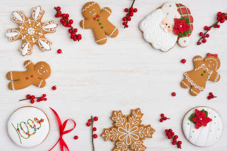 Various decorated gingerbread cookies and holly berries on wooden background