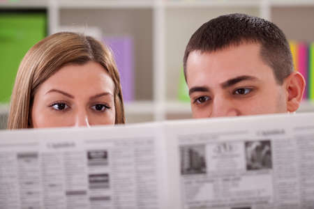newspaper reading: Couple reading news in room
