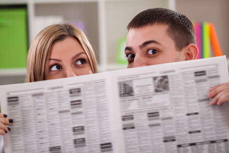 peeping: Couple peeping behind a newspaper Stock Photo