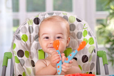 baby cutlery: Smiling baby eating with spoon and fork