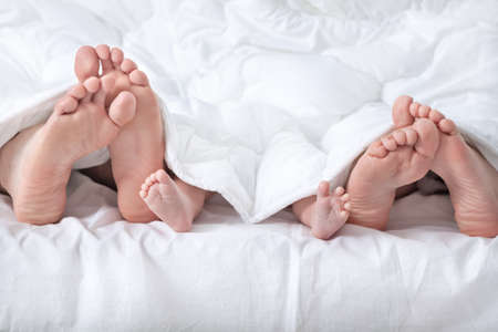 bed feet: Funny family feet under the blanket