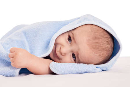 Little adorable baby lying on bed under blue towel isolated photo
