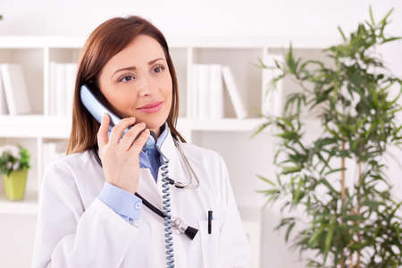 scheduling: Smiling female doctor talking with patient and scheduling Stock Photo