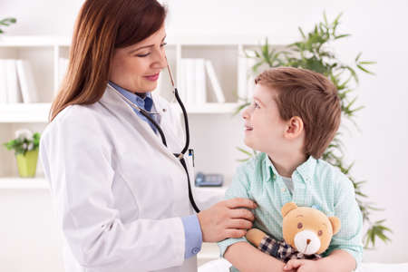 doctor woman: Beautiful female doctor examining smiling child in office Stock Photo