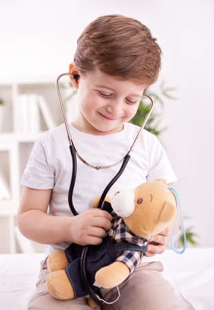 pediatric nurse: Adorable cute child with stethoscope of doctor examining teddy bear Stock Photo