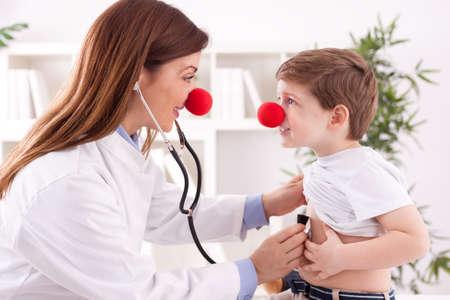 enfermedades del corazon: Hembra sonriente médico payaso escuchar corazón paciente Foto de archivo