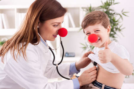 clown nose: Female doctor examining success child with finger up Stock Photo
