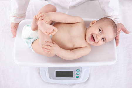 Measuring smiling beautiful comfortable little baby child Stock Photo
