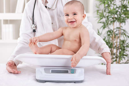 weighing: Happy smiling baby child in pedrician office, measuring weight Stock Photo