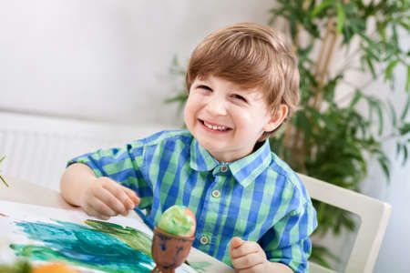 2 5: Adorable smiling happy child boy painting on paper and egg