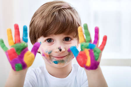 Cute little child boy with colored hands