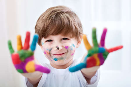 making faces: Happy smiling beautiful child playing with colors Stock Photo