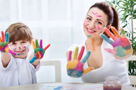 Happy smiling family with colored hands enjoy at home