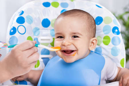 feed: Smiling happy adorable baby eating fruit mash in the kitchen