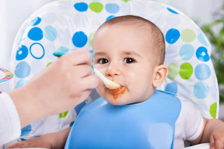 baby eating: Dirty cute baby enjoy when eating food in kitchen