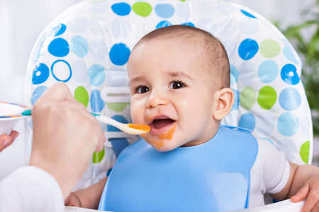 Smiling happy baby child eating with spoon Stock Photo