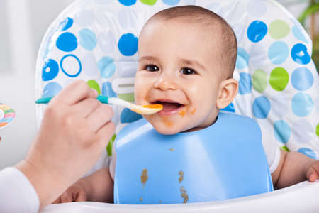 likes: Smiling  messy baby likes to eat Stock Photo