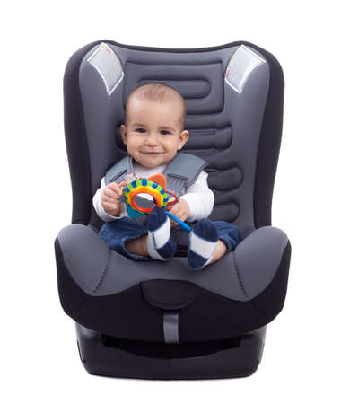 Adorable little kid sitting in a car seat, isolated Reklamní fotografie