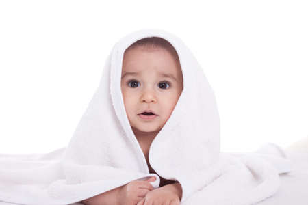 Cute infant baby under the white towel isolated on white photo