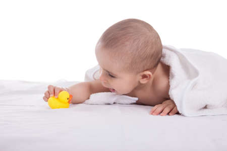 Beautiful infant playing with small yellow duck after shower photo