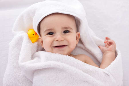Adorable baby smiling wrapped in white towel with yellow duck, isolated on white photo