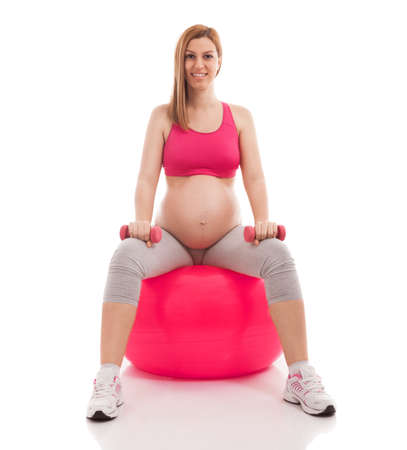 limbering: Pregnant beautiful woman exercise with ball and dumbbells isolated on white Stock Photo