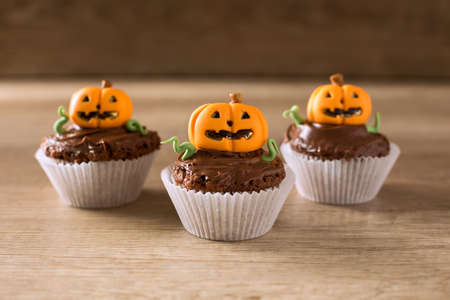 Homemade Jack Olantern Pumpkin cupcakes on wood background