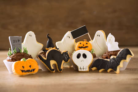 Spooky Halloween cookies and cupcakes background