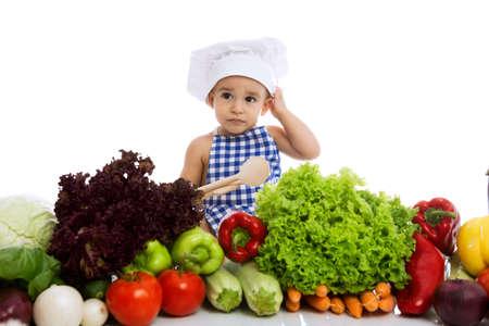 niños comiendo: Niño pequeño en el sombrero de chef con cuchara de cocina y verduras aislados