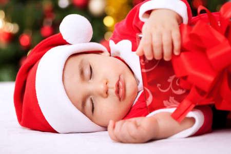 xmas baby: Sleeping baby child santa holding gifts and resting