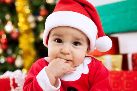 mouth close up: Cute baby santa claus with fingers in mouth close up Stock Photo