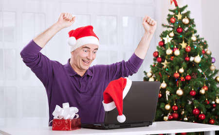 christmas hat: Happy smiling senior man with santa claus hat shopping online for christmas holiday