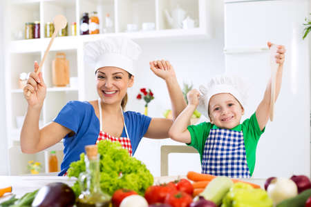 Smiling happy beautiful family ready for cook in kitchen Imagens