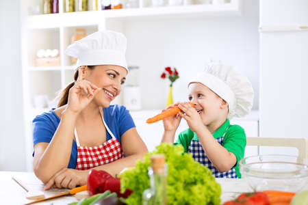 happy mom: Beautiful attractive mother and child playing with vegetables at home